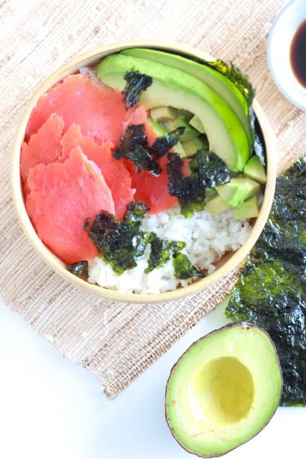 Sushi bowl made from white rice, lox, avocado and seaweed snacks