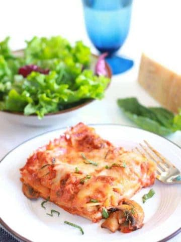 Square of vegetable lasagna with a salad on the side