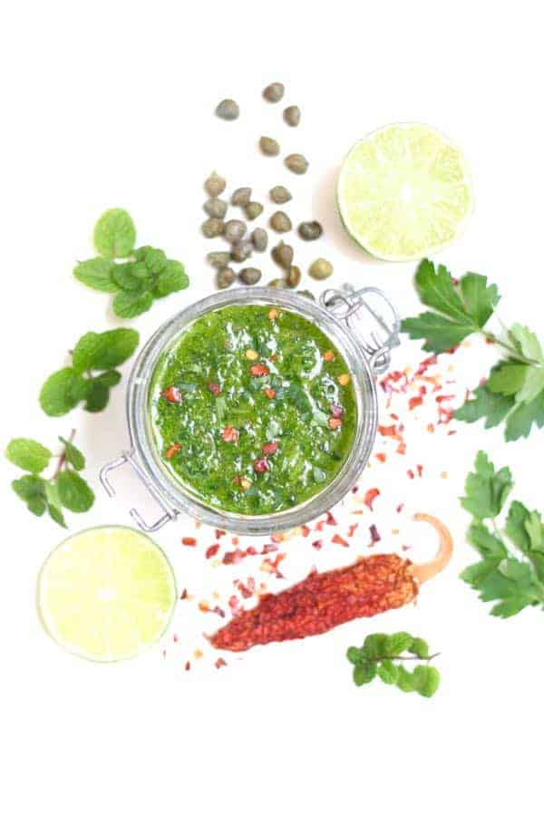 Small glass jar filled with parsley-lime dressing. Ingredients surrounding the bowl are capers, parsely, mint, hot pepper flakes and lime