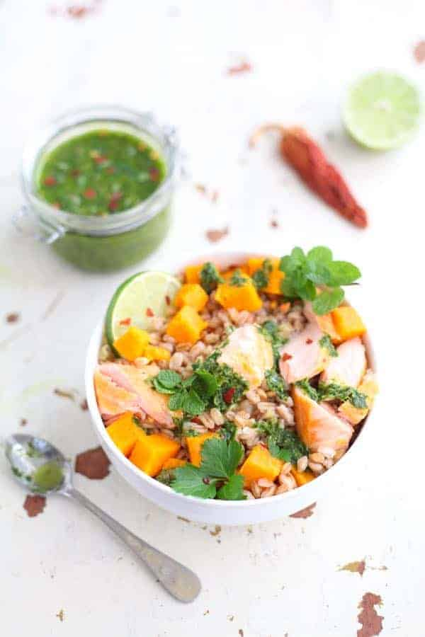 Bowl filled with farro, salmon and sweet potatoes. Parsley lime dressing poured on top.