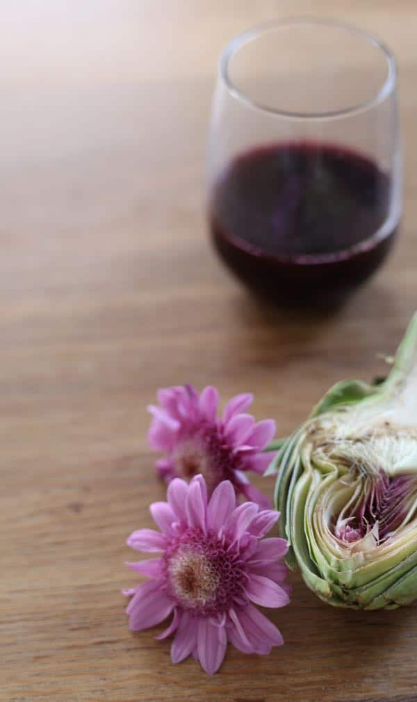 Glass of wine and pink flower with a halved artichoke