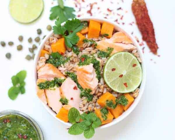 Close up of a bowl filled with farro, salmon and sweet potato pieces. Parsley-lime dressing poured on top.
