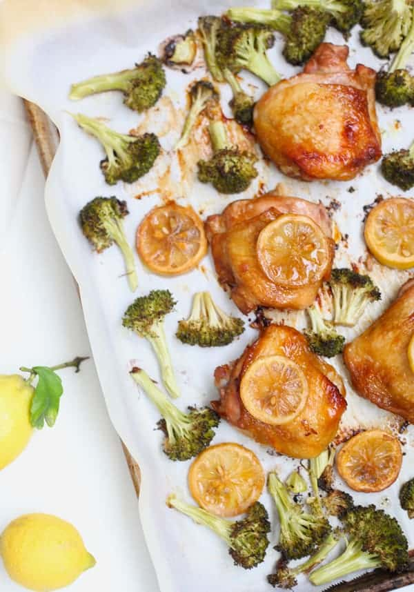A sheet pan with roasted soy sauce chicken thighs and broccoli garnished with lemon