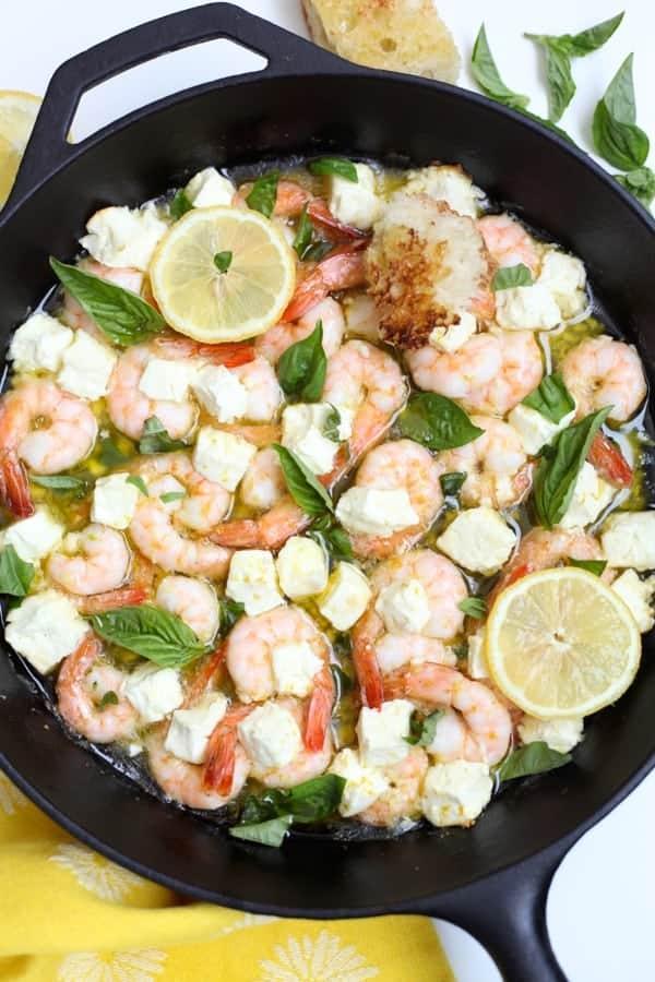 Black cast iron skillet with roasted shrimp, feta, olive oil and garlic with fresh basil