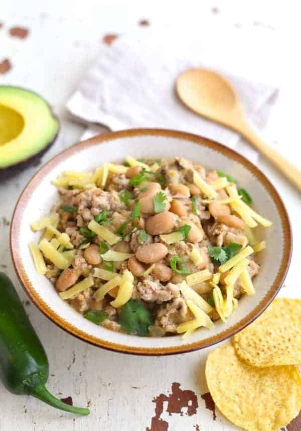 White bean and turkey chili in a bowl garnished with cilantro and grated cheese
