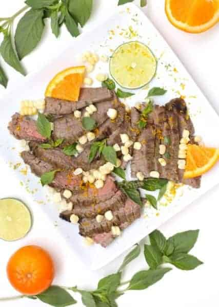 White plate with flank steak and corn, with limes, oranges and basil around the plate