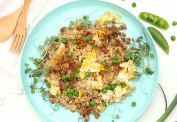 Fried rice on a plate with frozen peas, scrambled egg and tempeh