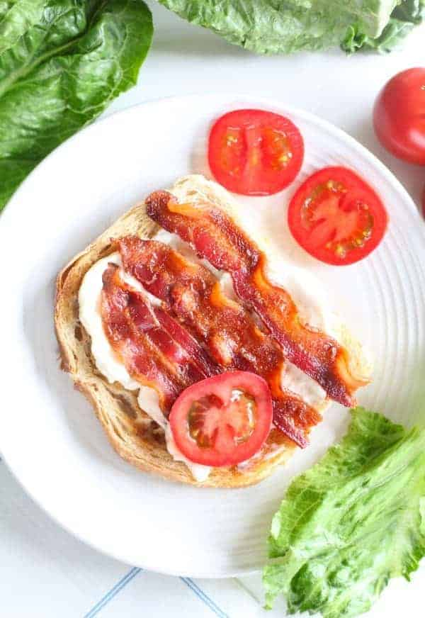 Slice of toasted sourdough bread spread with mayonnaise and topped with slices of tomato