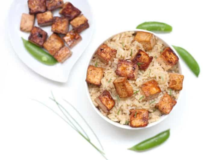 Seared tofu over brown rice in white bowl surrounded by snap peas and chives