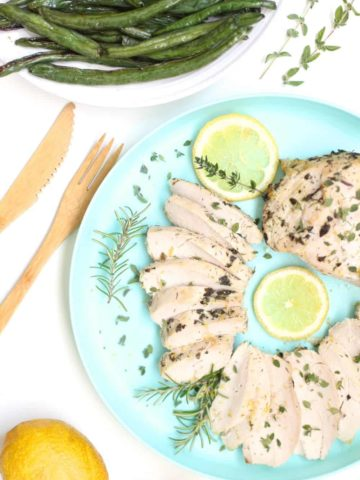 Herb-flecked Greek chicken breasts on a plate