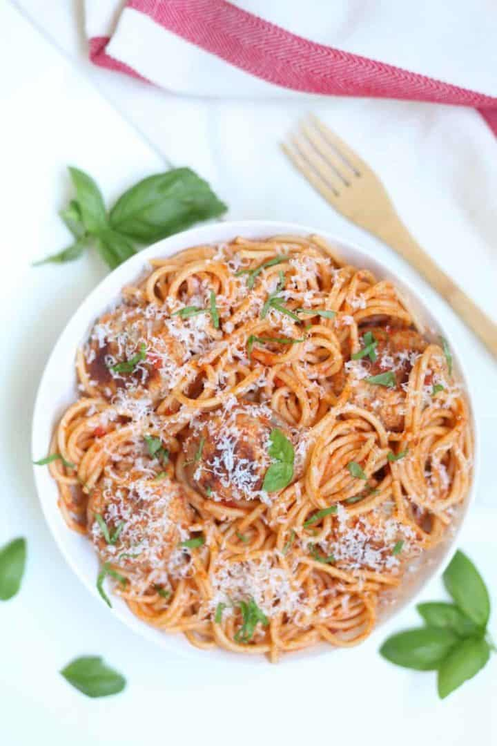 A white bowl filled with spaghetti, meatballs and red sauce