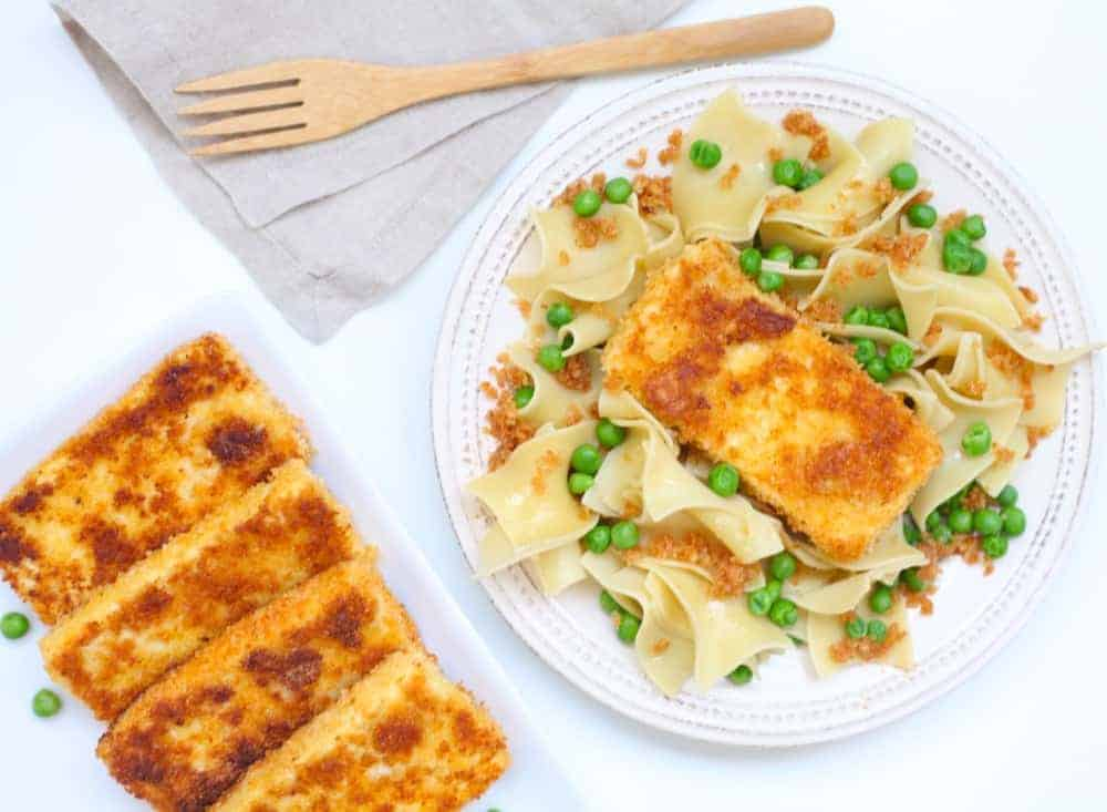 Slices of crispy, browned tofu fried in breadcrumbs on a white plate with buttered egg noodles and green peas