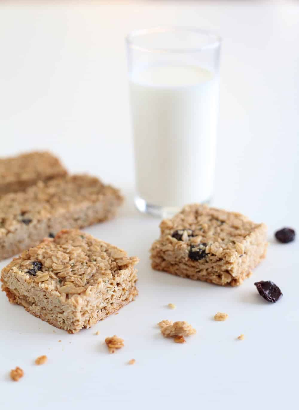 Tahini and dried cherry granola bars next to a glass of milk