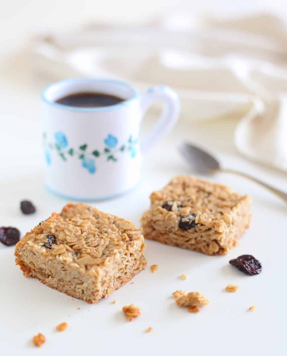 Two tahini cherry granola bars in front of a cup of coffee