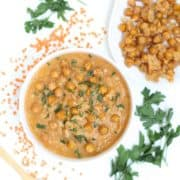 Red lentil soup in a white bowl topped with crispy parmesan chickpeas