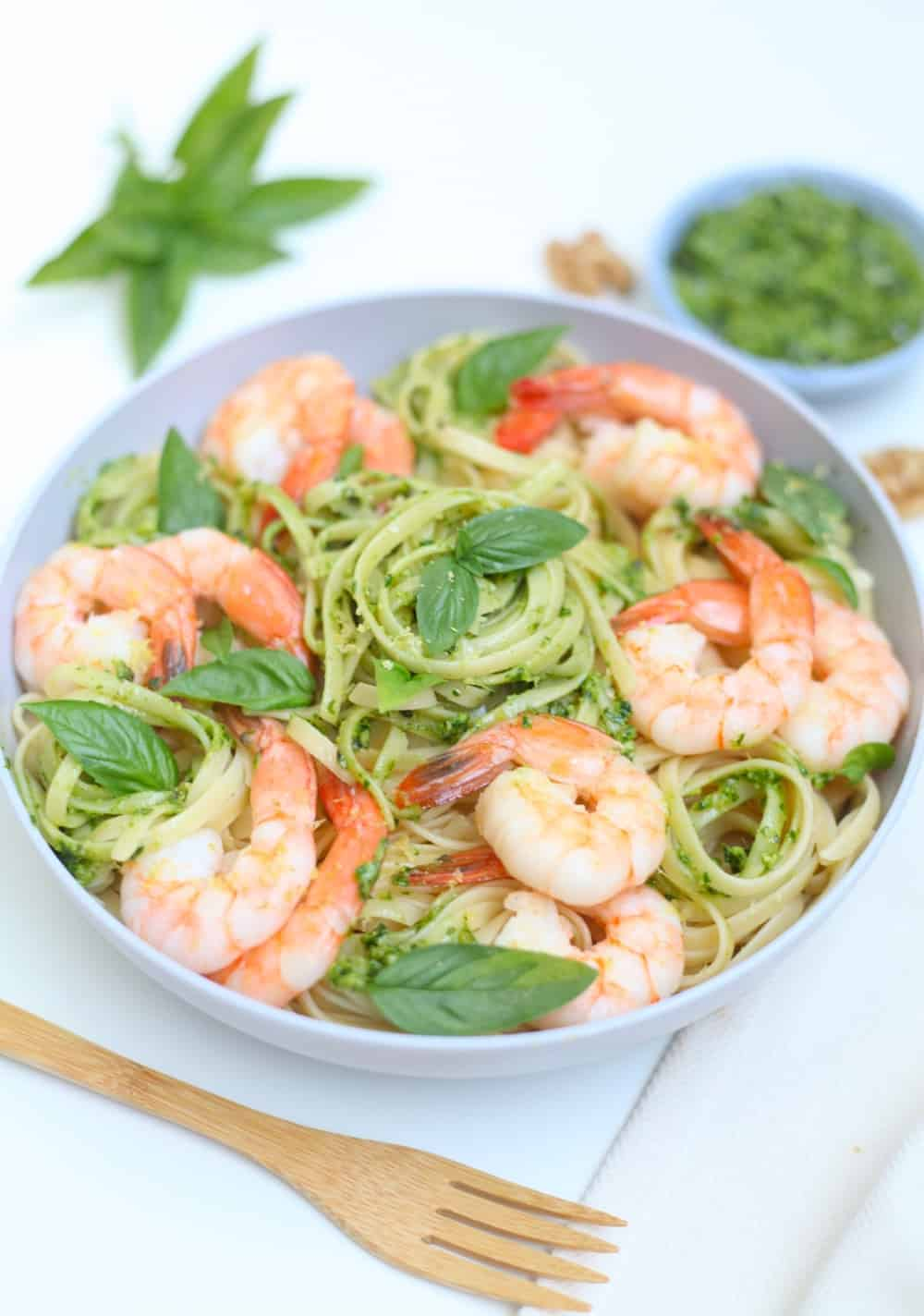 Gray bowl filled with linguine and shrimp tossed in arugula walnut pesto