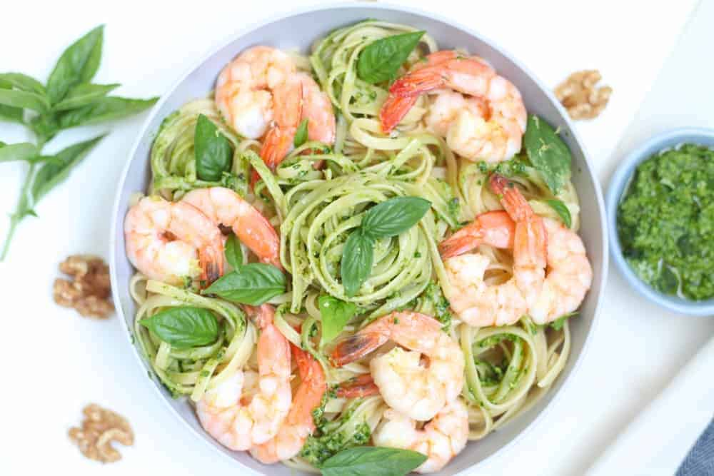 Gray bowl filled with fettuccine and shrimp tossed in arugula walnut pesto