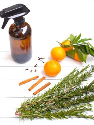 A glass spray bottle filled with natural kitchen cleaner on a white background surrounded by oranges, rosemary cloves and cinnamon sticks