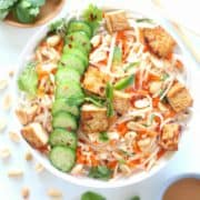 White bowl filled with rice noodles, raw cabbage and carrots, tofu and peanut lime dressing