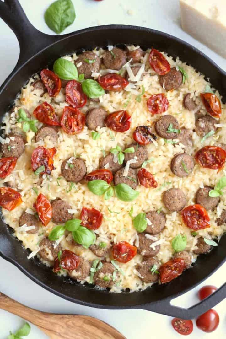 Black cast iron skillet filled with oven-baked sausage risotto, roasted cherry tomatoes and fresh basil