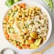 White bowl filled with chickpea stew, chicken and potatoes