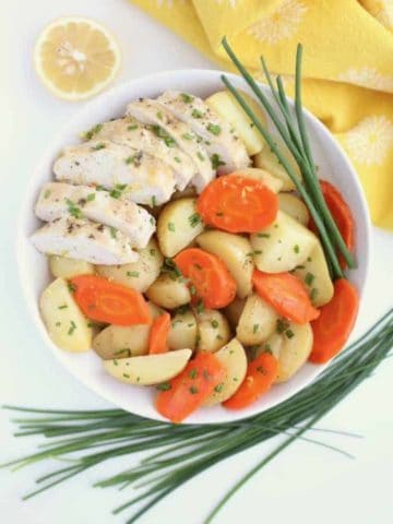 White bowl filled with sliced chicken breast, potatoes and carrots, with chives around the bowl