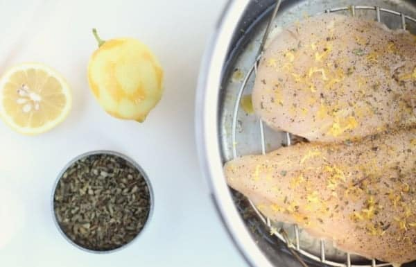 Open Instant Pot with two raw chicken breasts setting on a trivet above water, with lemon garlic seasoning