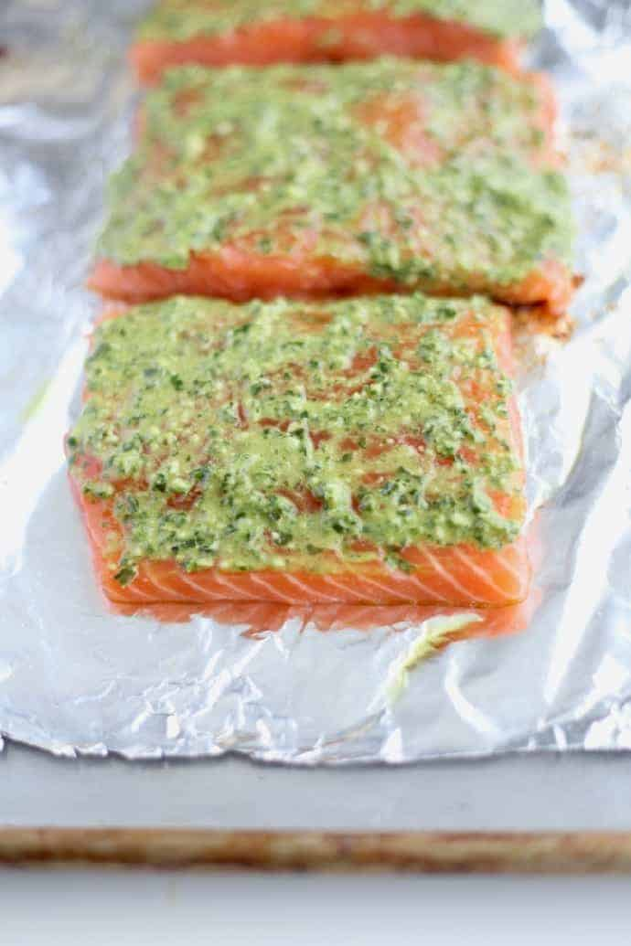 Sheet pan with three uncooked salmon fillets topped with pesto mayonnaise