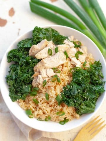 White bowl filled with Instant Pot cooked brown rice, sliced chicken thigh with kale and green onion