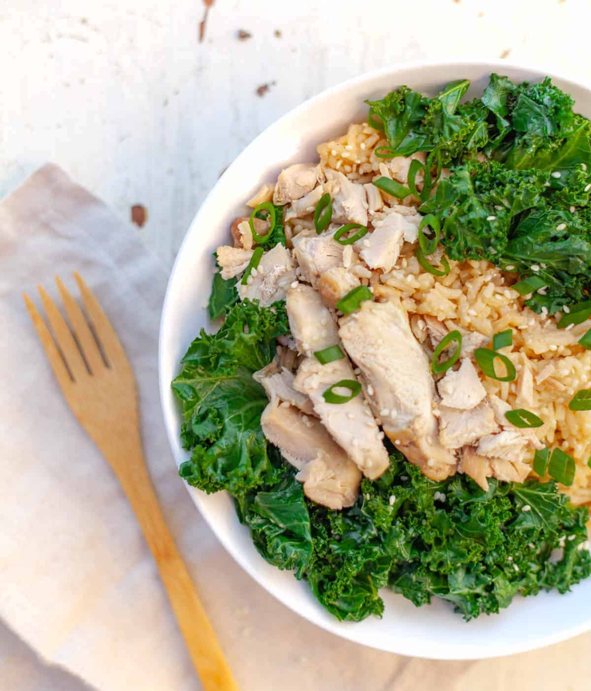 A white bowl filled with instant pot cooked brown rice and sliced chicken thigh with kale and green onion
