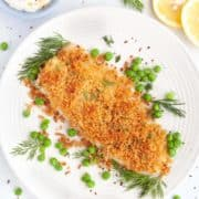 White plate with a fillet of baked panko fish, a small blue bowl filled with creme fraiche and mustard sauce on the side