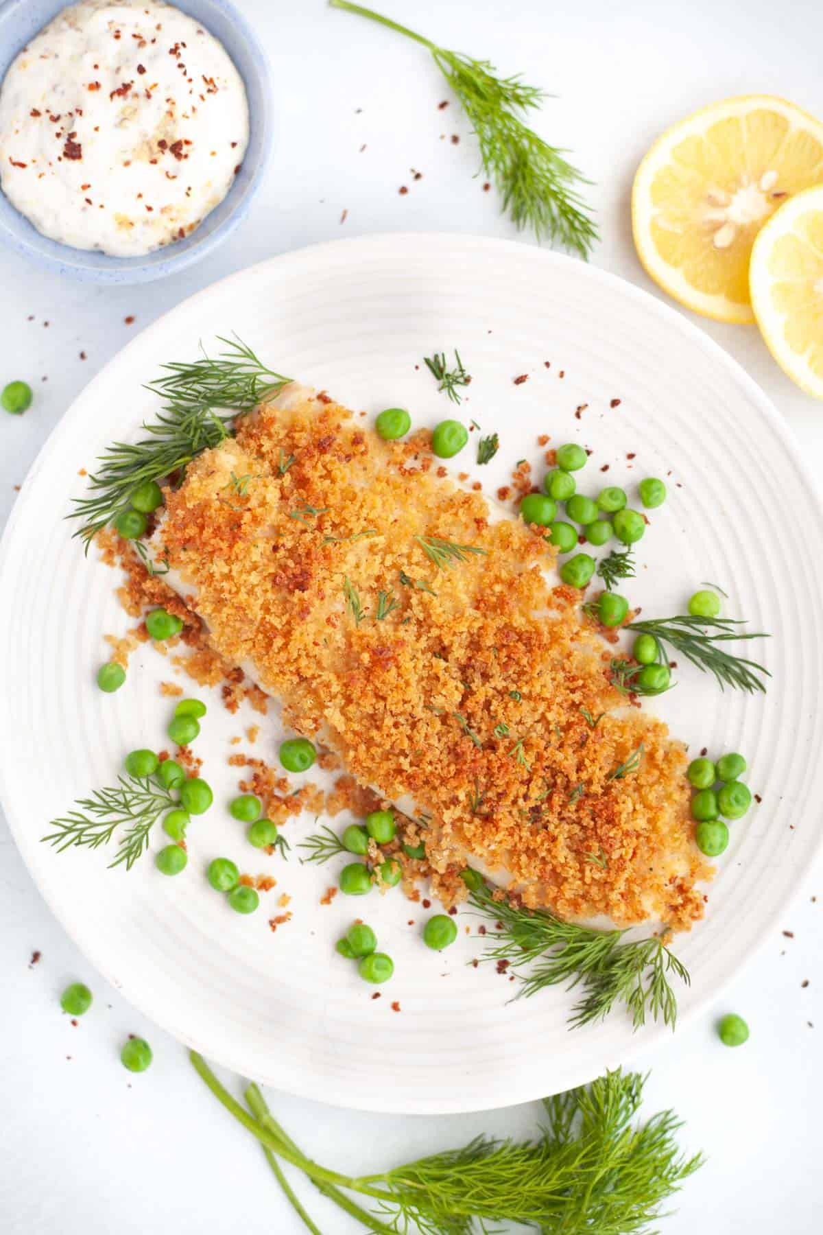 White plate with a fillet of baked panko cod, a small blue bowl filled with creme fraiche and mustard sauce on the side