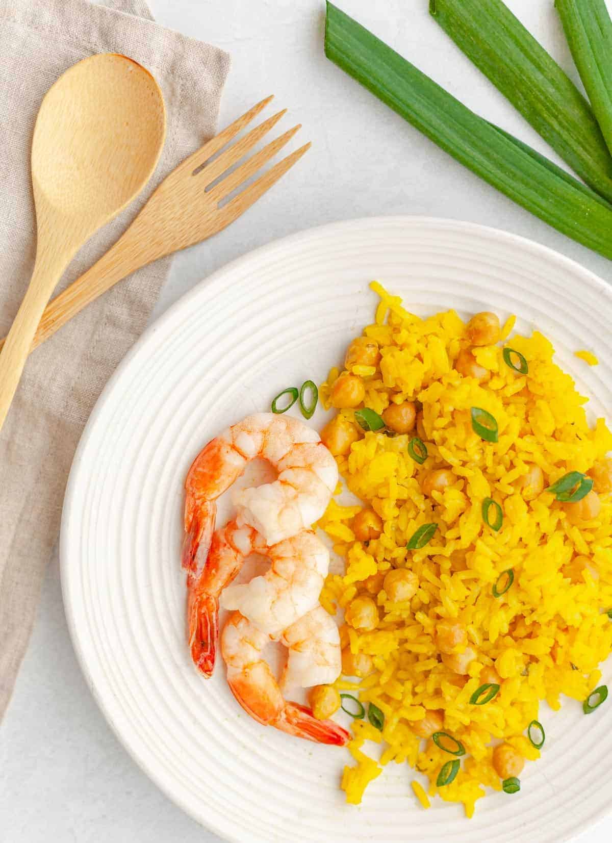 Yellow turmeric coconut rice on a plate with shrimp garnished with green onions