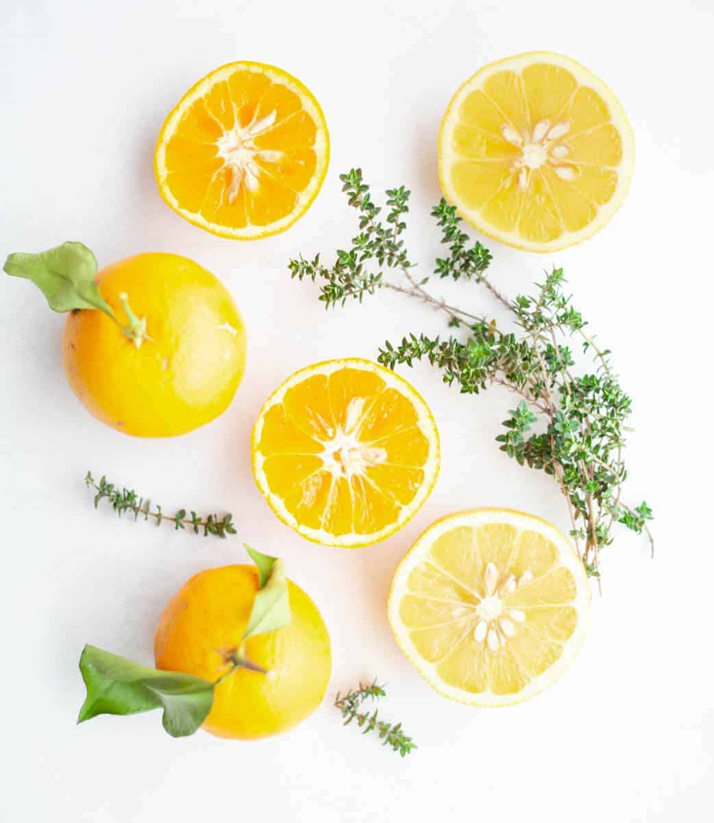 sprigs of thyme and oranges and lemons cut in half on a white background