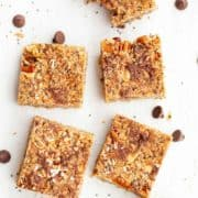 Squares of granola bars made from almond butter, dark chocolate, coconut, pecans and chia seeds