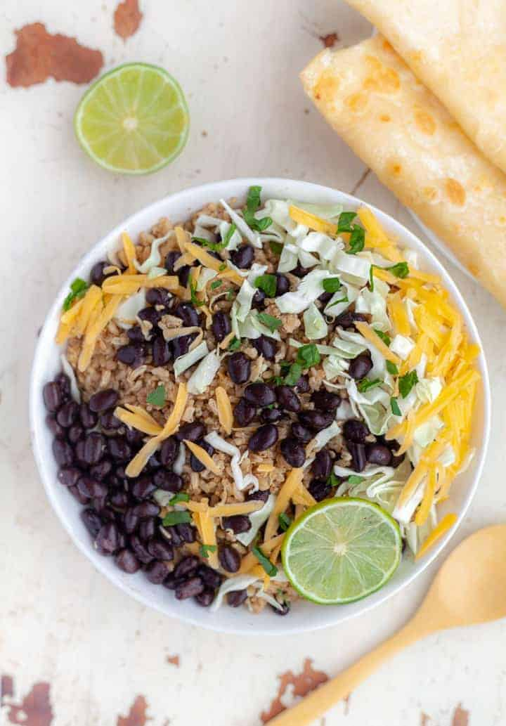 White bowl filled with Instant Pot brown rice and quinoa topped with black beans, shredded cabbage and grated cheddar cheese