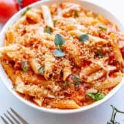 Instant Pot Chicken Parmesan Pasta in a bowl, made from penne pasta, tomato sauce, melted cheese and chicken tenders