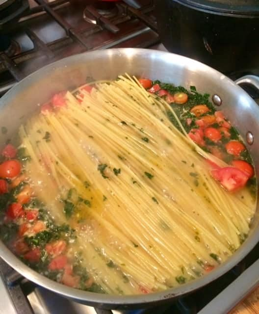 A skillet simmering spaghetti noodles, kale and tomatoes