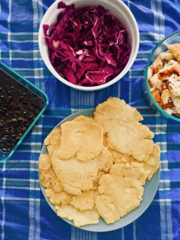 Blue plaid tablecloth with a plate of homemade corn tortillas, a bowl of black beans and a bowl of purple cabbage