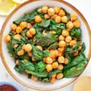 Brown bowl filled with chickpeas and spinach simmered in thick tomato sauce