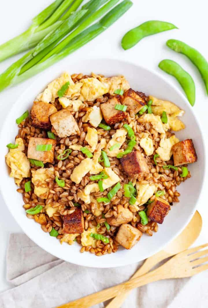 White bowl filled with barley and egg fried rice with tofu and scallions