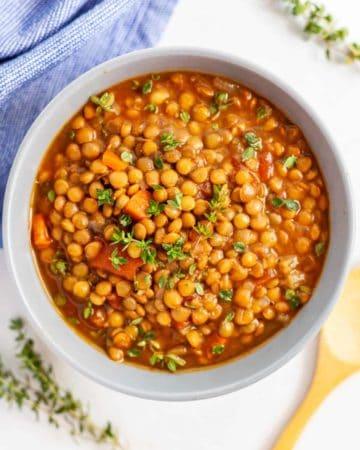 White bowl filled with crockpot lentil soup garnished with thyme