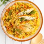 A bowl of turmeric rice with flecks of carrot and dill with slices of chicken