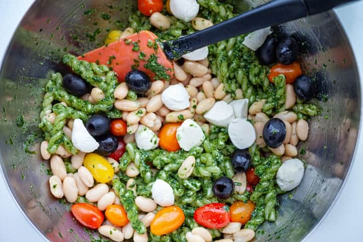Mixing together ingredients for Spinach Pesto Pasta Salad with White Beans, Mozzarella and Tomatoes