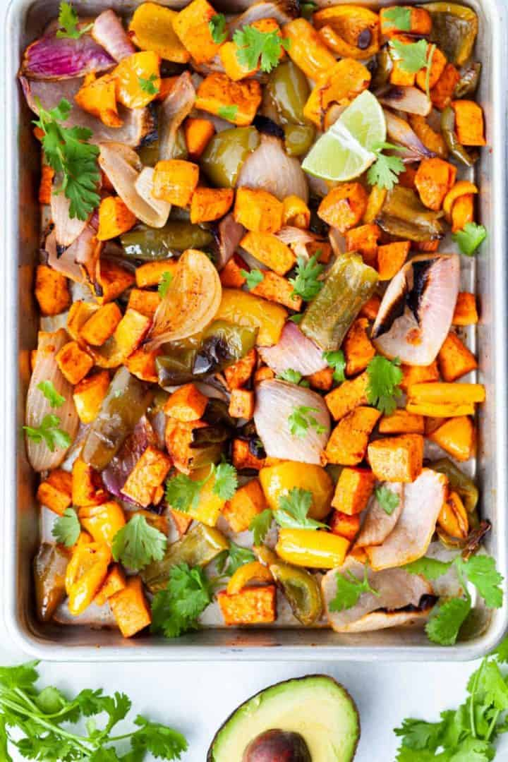 Sheet pan of roasted vegetarian fajita ingredients - sweet potato, bell pepper, red onion and spices
