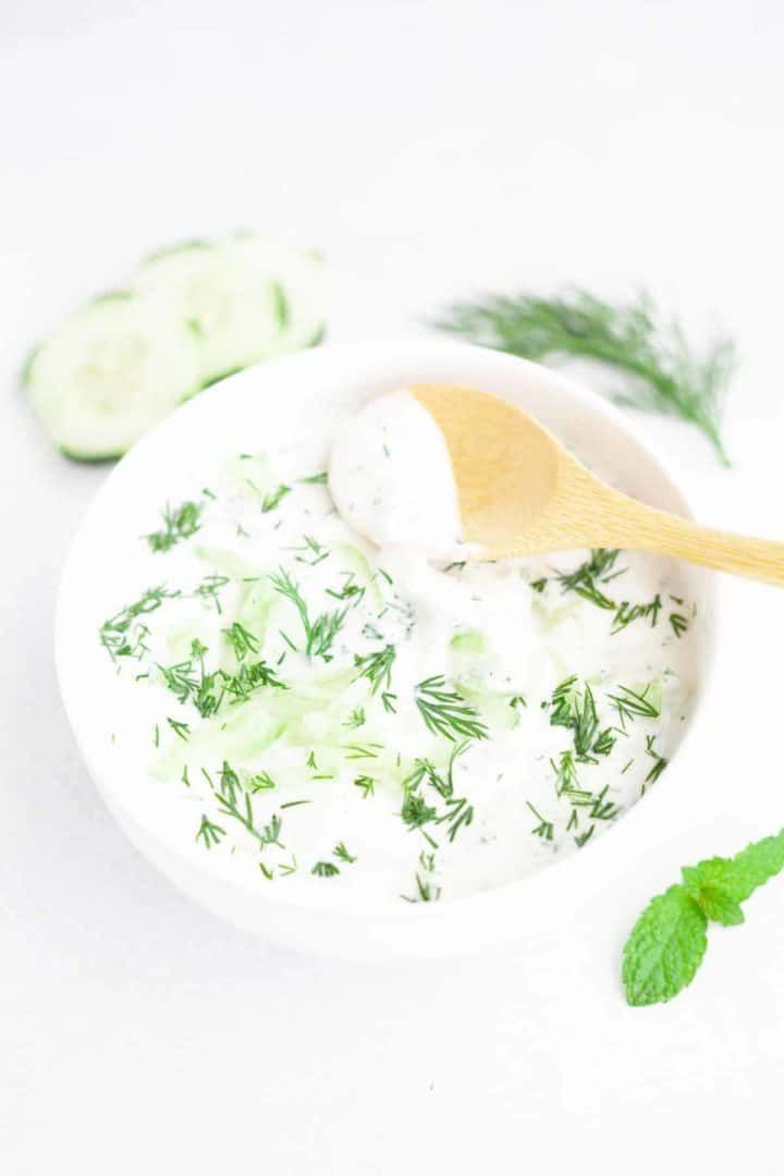 White bowl filled with cold yogurt sauce flavored with dill and grated cucumber