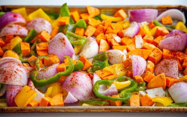 Sheet pan of raw vegetarian fajita ingredients, chopped sweet potatoes, bell pepper and red onion with spices