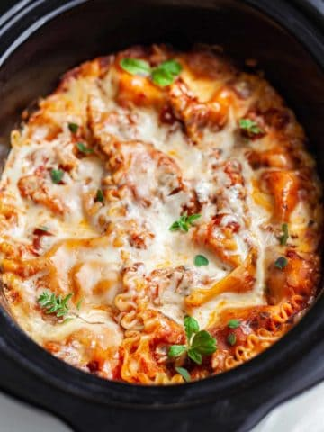 A slow cooker filled with cooked vegetarian lasagna with melted mozzarella cheese on top