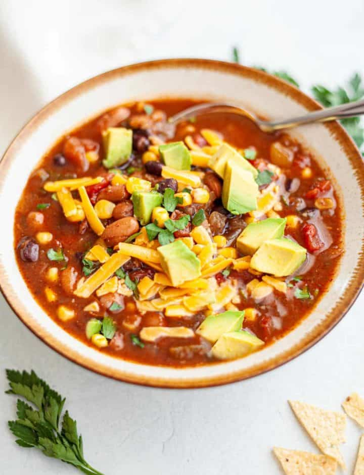 Bowl of Instant Pot Vegetarian Chili made with pinto and black beans, tomatoes, corn and spices