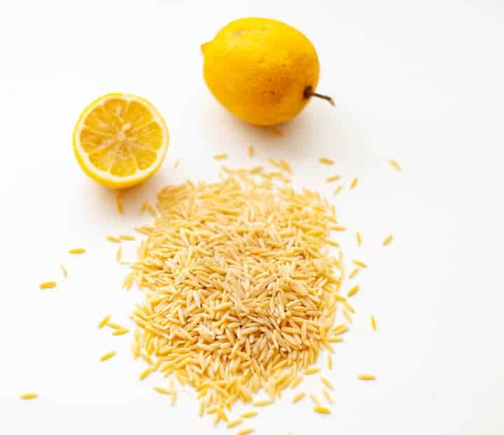 Uncooked orzo pasta on a white background in front of a lemon cut in half